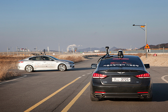 Two self-driving cars at the crossroads are communicating via 5G network to decide which vehicle to first pass through the congested area
