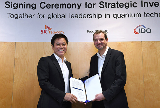 Park Jung-ho, CEO and President of SK Telecom, and Grégoire Ribordy, CEO of IDQ, are holding hands during a meeting to discuss SK Telecom's investment.