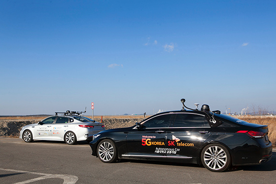 Two 5G self-driving cars are driving side by side on the road
